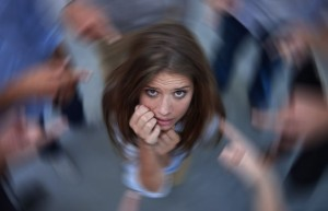 Conceptual shot of an anxious young woman in the middle of a circle of accusing coworkers